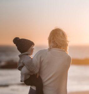 moeder houdt kind vast bij zonsondergang op het strand